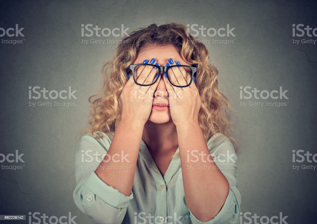 Closeup portrait young woman in glasses covering face eyes stock photo