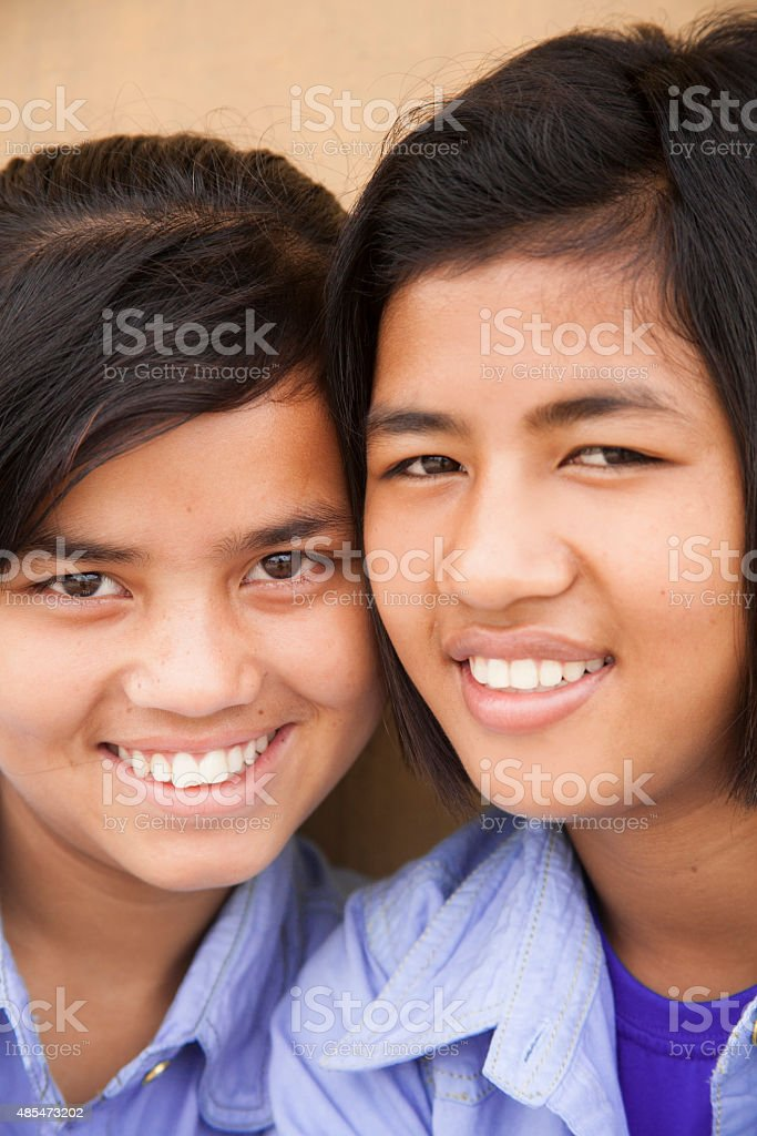 Close-up, portraits. Sisters or friends posing outdoors. Indian, Asian descent. stock photo