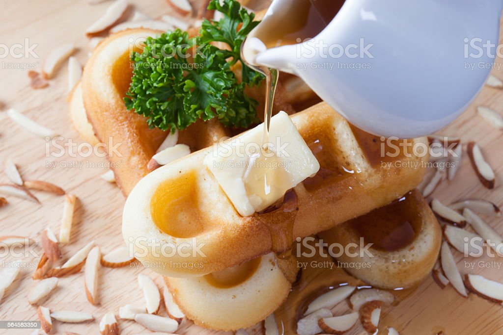 Close-up pouring honey from top of waffles and nut stock photo