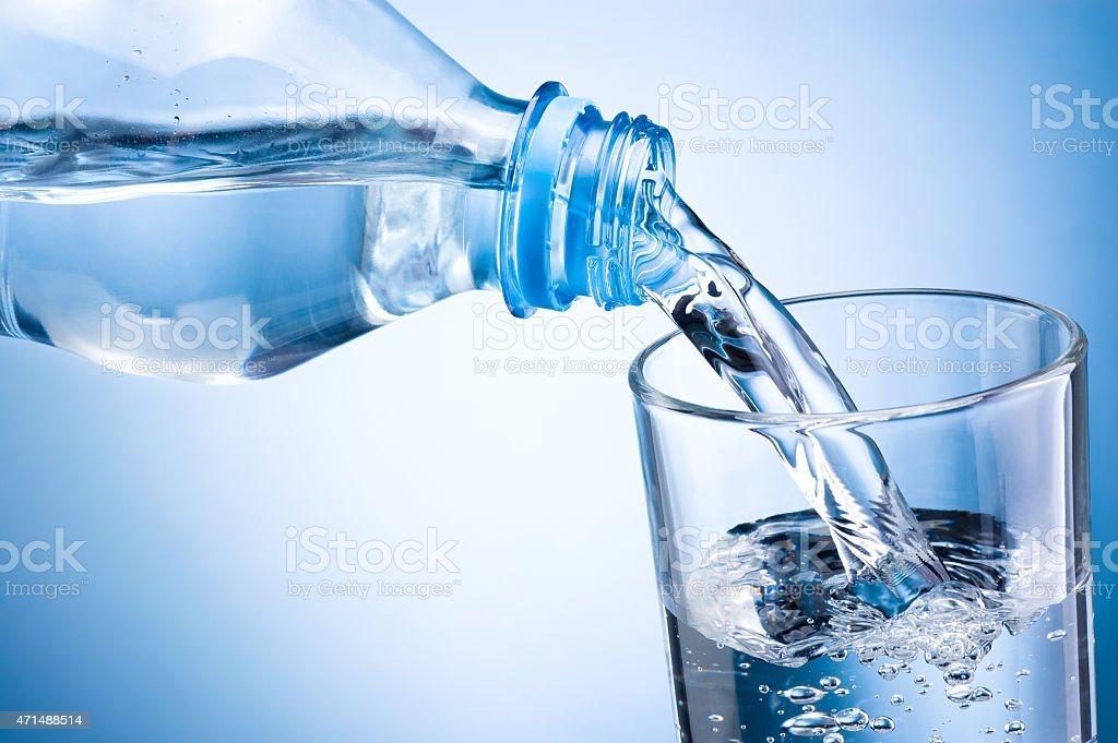 Close-up pouring water from bottle into glass on blue background stock photo