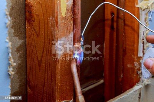 Closeup professional master plumber hands soldering copper pipes gas burner pipe line repair, professional plumber master, pipe leakage