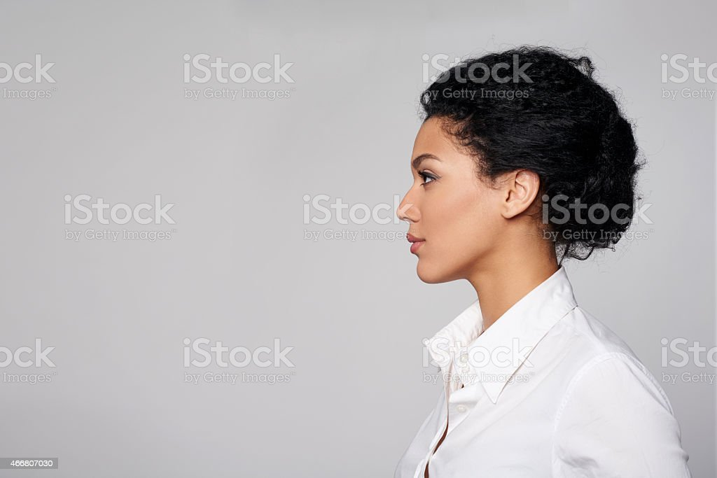 Closeup profile of business woman looking forward Closeup profile of confident business woman looking forward isolated on gray background 2015 Stock Photo