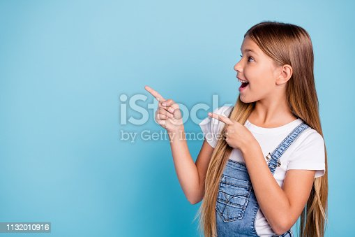 istock Close-up profile side portrait of her she nice cute attractive cheerful amazed glad straight-haired blonde girl pointing two fingers looking aside copy space isolated on blue pastel background 1132010916