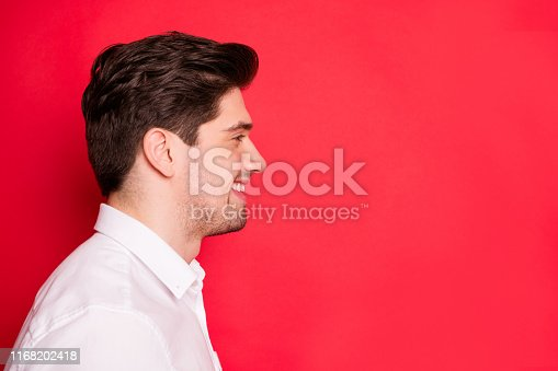 1165538246 istock photo Close-up profile side view portrait of his he nice attractive cheerful cheery guy student copy empty blank space advert ad isolated over bright vivid shine red background 1168202418