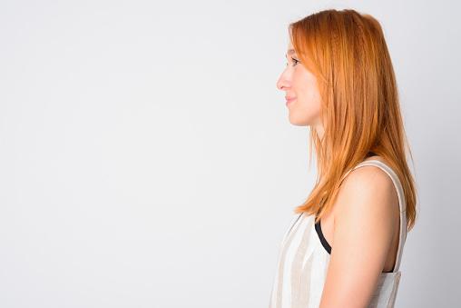 Closeup profile view of young beautiful redhead woman