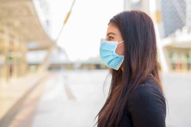 Closeup profile view of young Indian woman with mask for protection from corona virus outbreak in the city stock photo