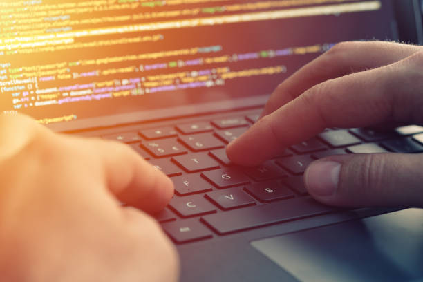 Closeup programmer coding on screen. Hands coding html and programming on laptop screen, web development, developer stock photo