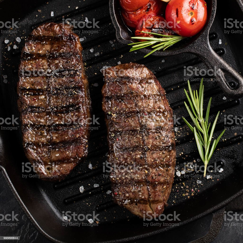 Closeup ready to eat steak Top Blade beef breeds of black Angus with grill tomato, garlic and on a wooden Board. The finished dish for dinner on a dark stone background. Top view stock photo