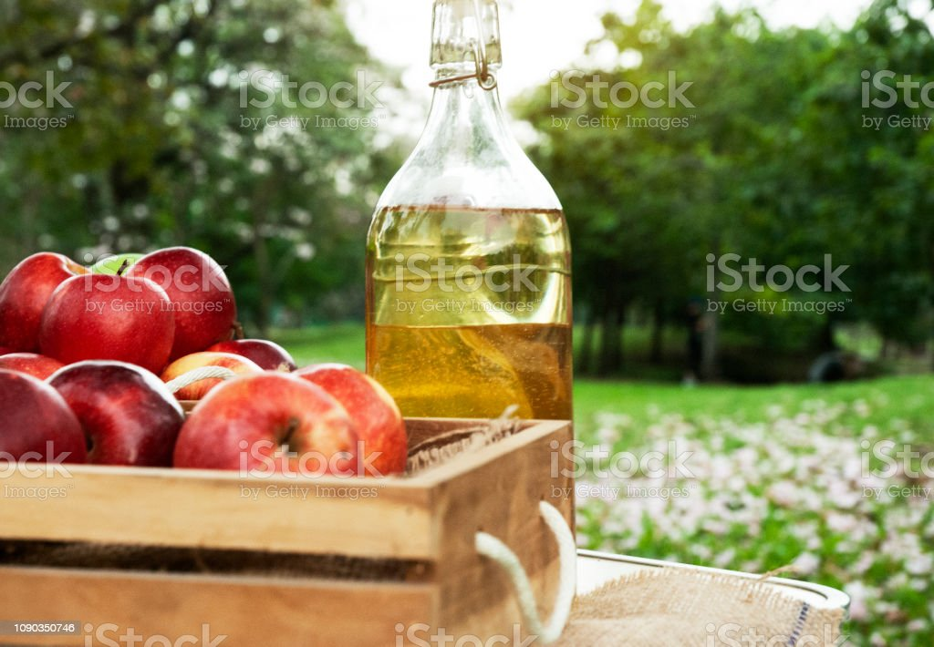 Close-up Red apple and apple oil on wood table. stock photo