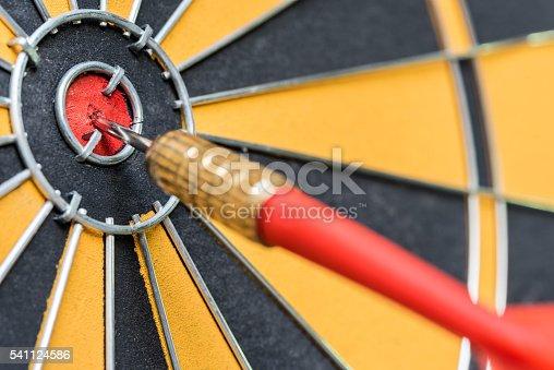 886643538 istock photo closeup red dart arrow hitting in target bullseye of dartboard 541124586