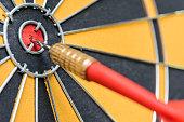 istock closeup red dart arrow hitting in target bullseye of dartboard 541124586