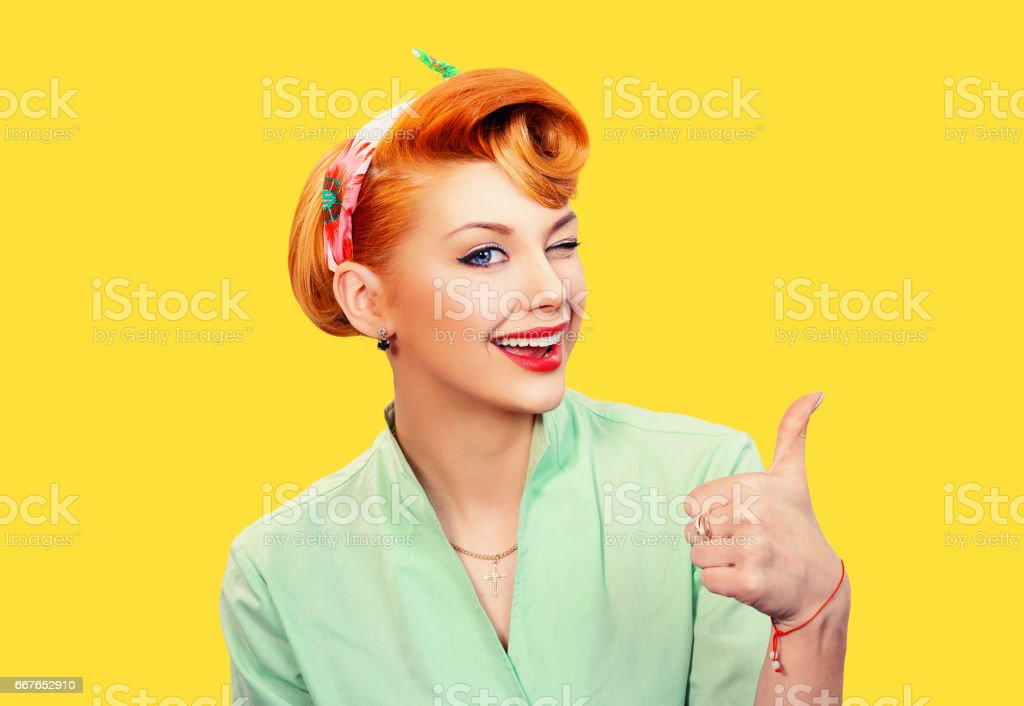 Closeup red head young woman pretty pinup girl green button shirt giving thumbs up sign gesture looking at you camera isolated yellow background retro vintage 50's style. Human emotions body language stock photo