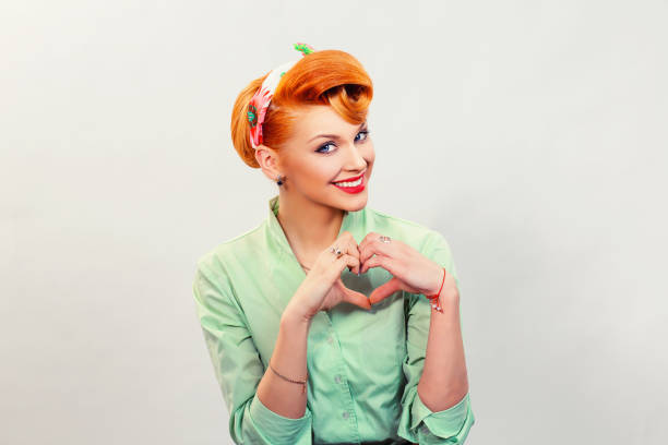 closeup red head young woman pretty pinup girl green button shirt giving thumbs up sign gesture looking at you camera isolated white background retro vintage 50's style. human emotions body language - pin up girl stock pictures, royalty-free photos & images