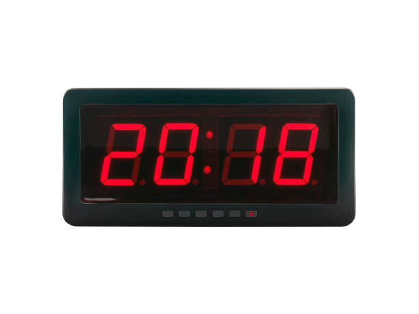 closeup red led light illumination numbers 2018 on black digital electric alarm clock face isolated on white background stock photo