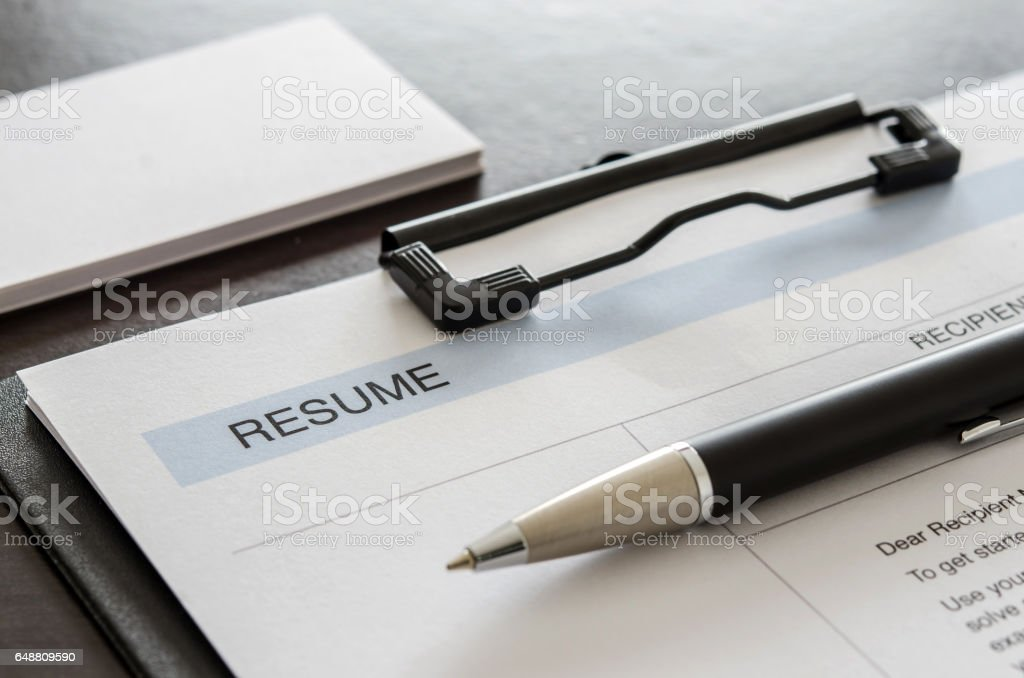 Close-up resume form, pen and business card on wooden desk. stock photo