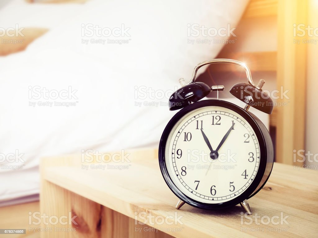 Closeup retro alarm clock on Bedside table with bed background and copy space, retro style stock photo