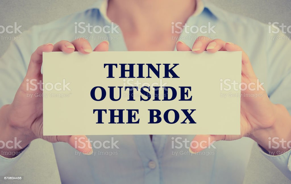 Closeup retro image businesswoman hands holding white sign or card with message think outside the box stock photo