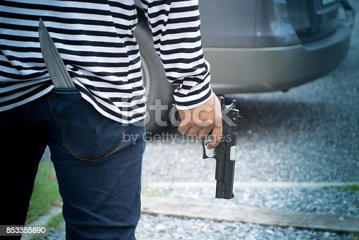 istock Closeup robber holding a gun walking to the car for rob 853355690