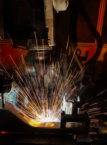 Closeup robot welding automotive part in factory.