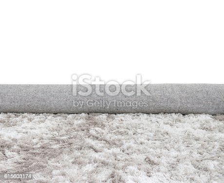 istock Closeup roll gray fabric carpet isolated on white background 615603174