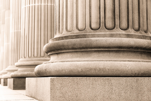 istock Closeup row of capital columns, background with copy space 615594330