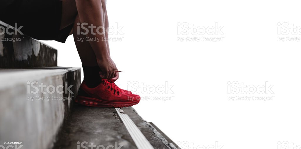 Close-up runner tying shoelace on the steps, isolated on white background with copy space, healthy lifestyle stock photo