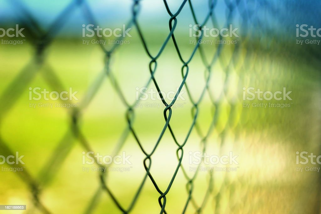Close-up section of a chain-link fence with field behind it stock photo
