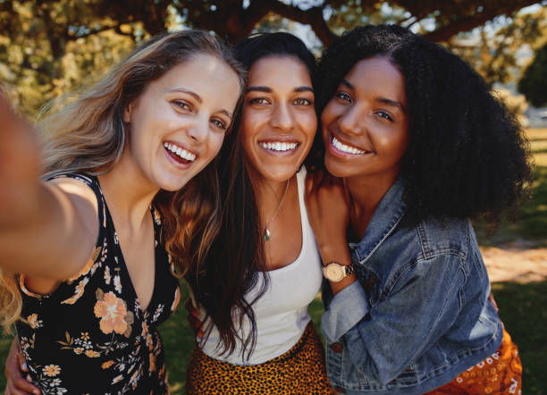nahaufnahme selbstporträt von lächelnden jungen multiethnischen freundinnen, die selfie im park machen - frauen, die an einem hellen tag ein selfie im park machen - freundin stock-fotos und bilder