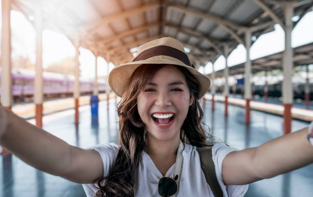 Close-up selfie-portrait of attractive girl with long hair standing at railway statioin stock photo