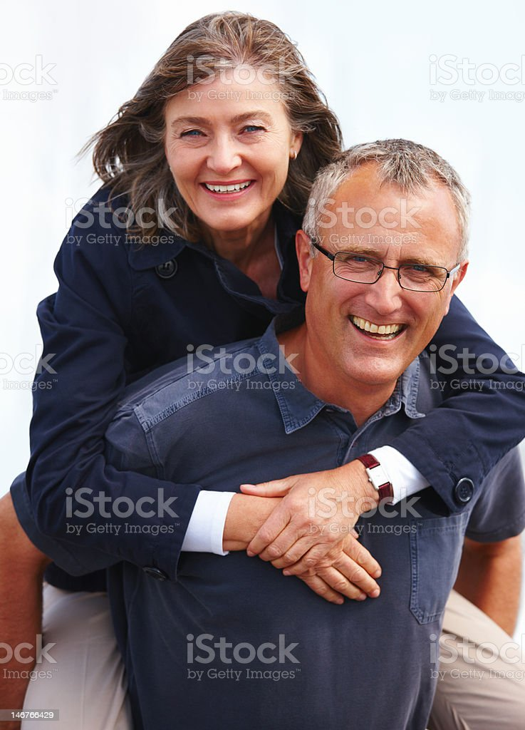 Close-up senior man giving piggyback to woman against white background royalty-free stock photo