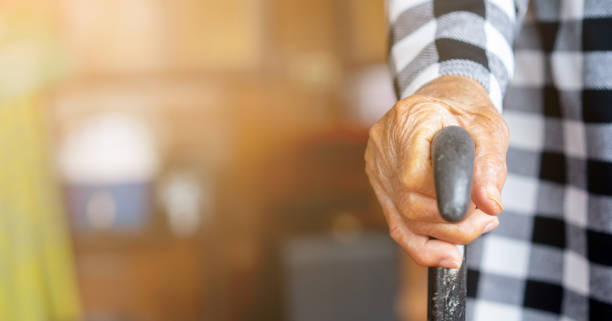 main de femme aînée de plan rapproché retenant la canne de marche pour aider à se tenir à la maison, mode de vie du concept vieillissant de personnes - une seule femme senior photos et images de collection