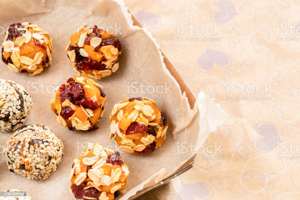 Close-up set of handmade energy balls are lying in cardboard box on...