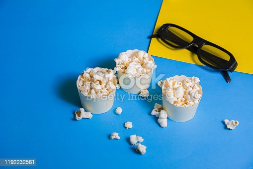 956942702 istock photo closeup shot of 3 mini small popcorn boxes cups full of fresh hot popcorn cinema movie theater 3d glasses black color on blue and yellow background 1192232561