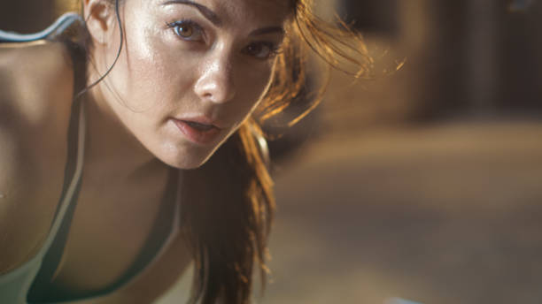 Close-up Shot of a Beautiful Athletic Woman Looks into Camera. She's Tired after Intensive Cross Fitness Exercise. stock photo