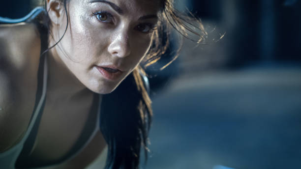 Close-up Shot of a Beautiful Athletic Woman Looks into Camera. She's Tired after Intensive Cross Fitness Exercise. Close-up Shot of a Beautiful Athletic Woman Looks into Camera. She's Tired after Intensive Cross Fitness Exercise. effort stock pictures, royalty-free photos & images