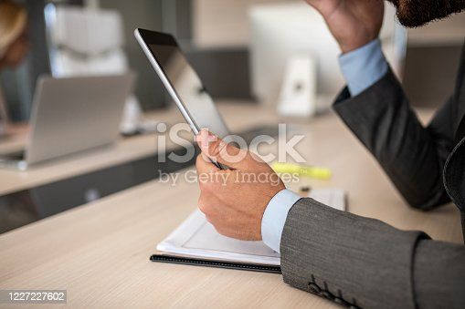 960164282 istock photo Closeup shot of a businessman analyzing statistics on a digital tablet in an office 1227227602