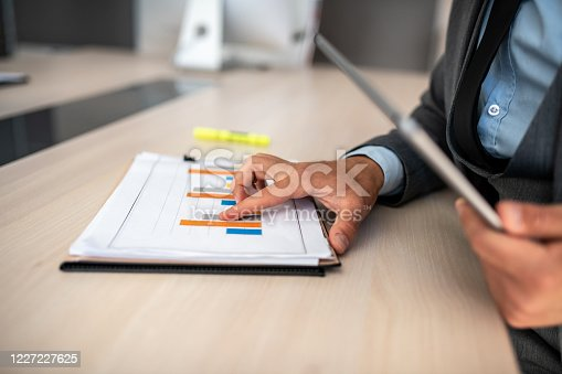 960164282 istock photo Closeup shot of a businessman analyzing statistics on a digital tablet in an office 1227227625