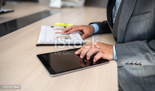 960164282 istock photo Closeup shot of a businessman analyzing statistics on a digital tablet in an office 1227227647