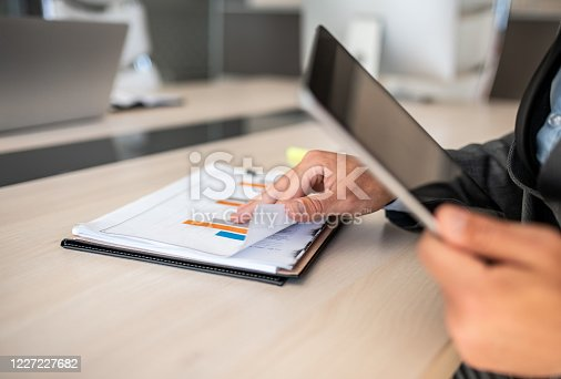 960164282 istock photo Closeup shot of a businessman analyzing statistics on a digital tablet in an office 1227227682