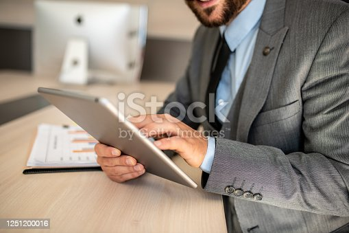 960164282 istock photo Closeup shot of a businessman analyzing statistics on a digital tablet in an office 1251200016