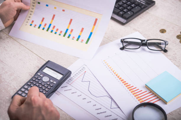 Close-up shot of a businessman holding statistics report and using calculator stock photo