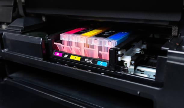 nahaufnahme einer cmyk-tinten-patronen in einem farbdrucker. - munition nachfüllen stock-fotos und bilder