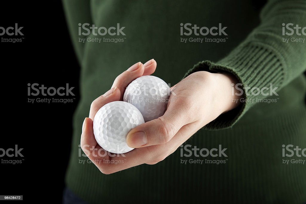 closeup shot of a female hand holding two golf balls royalty-free stock photo