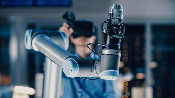 toma de primer plano de un brazo robótico futurista controlado por un ingeniero de desarrollo profesional con auriculares de realidad virtual y joysticks en un laboratorio de investigación de alta tecnología con equipos modernos - robótica fotografías e imágenes de stock