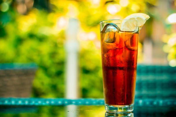 Close-up shot of a glass full with ice tea and cubes with a slice of lemon stock photo