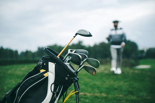 Close-up shot of a golf bag in a golf course. There is an unrecognizable defocused person in background, focus on the golf bag. Horizontal shot.
