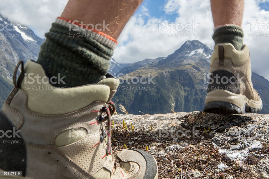 Closeup shot of a hiker's boots on mountain trail stock photo