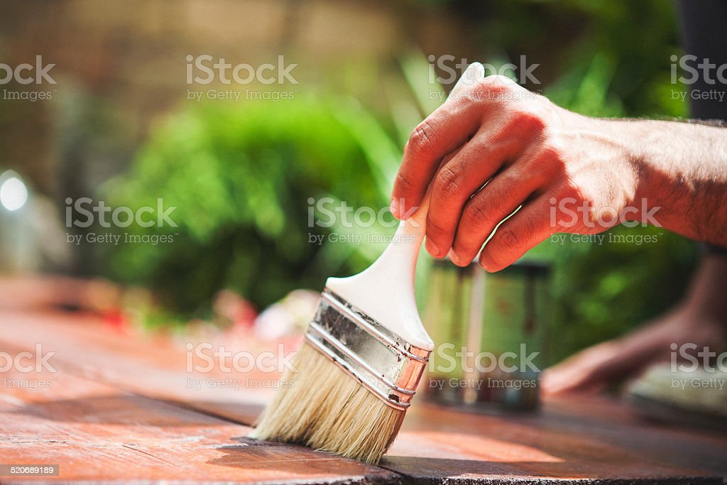 Closeup shot of a man painting with paint brush stock photo