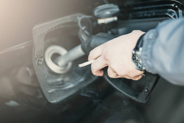 Close-up shot of a man's hand refueling fuel tanker of a car stock photo