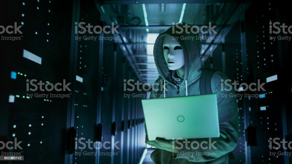Close-up erschossen von einem maskierten Hacker in ein Hoodie stehend in die Mitte des Data Center voller Rack-Servern und hacken es mit seinem Laptop. – Foto